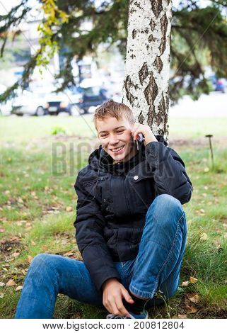 Happy Teenager call on the Phone in the Autumn Park