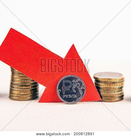 Piles of the Coins with Red Arrow Russian Ruble Down Concept