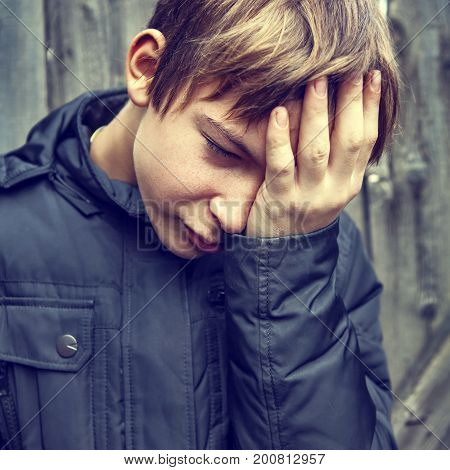 Toned Photo of Sad Kid on the Woooden Wall Background