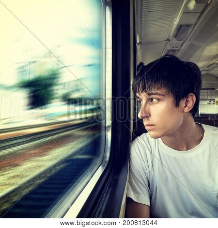 Toned Photo of Pensive Young Man sit in the Train