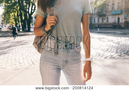 Cropped Image Of A Slender Girl In Jeans, A T-shirt And A Backpack In The City