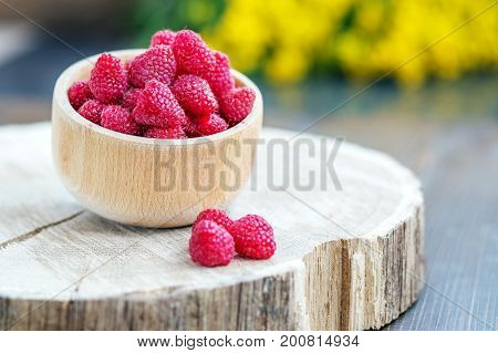 Tasty raspberries in a wooden bowl. Place for text. The concept is healthy food diet vegetarianism vitamins.