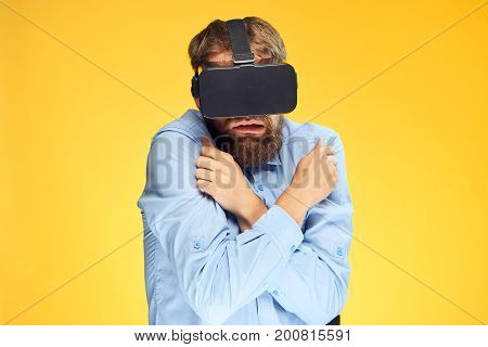 A young guy with a beard on a yellow background in virtual reality glasses.