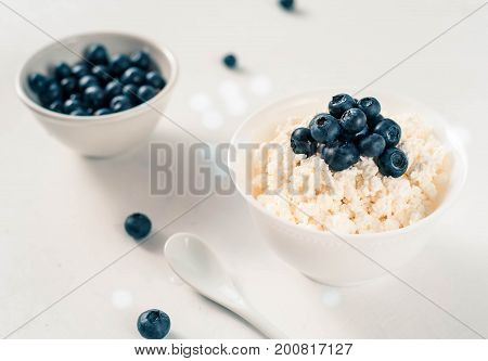 Cottage cheese with blueberries on wood white