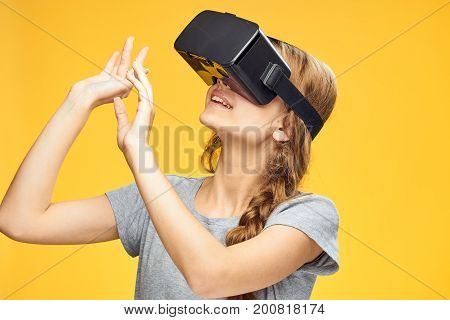 Beautiful young woman on a yellow background with virtual reality glasses.
