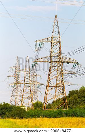 High-voltage Lines And Power Transmission Pylons In The Flat And Green Agricultural Landscape On A S