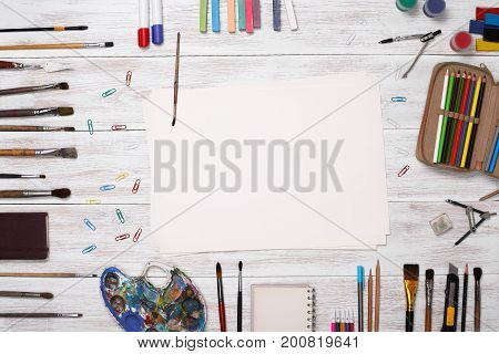 Top view art workplace with copy space. White, wooden table top view of the artist. On the table are perfect subjects for art, pencils, paints, crayons, colored paper, scissors, Stationery items.