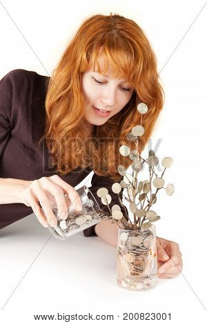 Red hair girl is adding coins into her money tree glass. Investments, revenue growth concept.