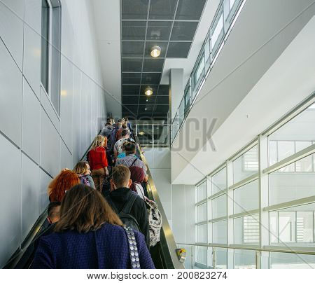 FRANKFURT GERMANY - AUG 8 2017: Rear view of commuters passengers on escalator in modern Frankfurt International iarport terminal commuting to the luggage area connecting flights and baggage claim