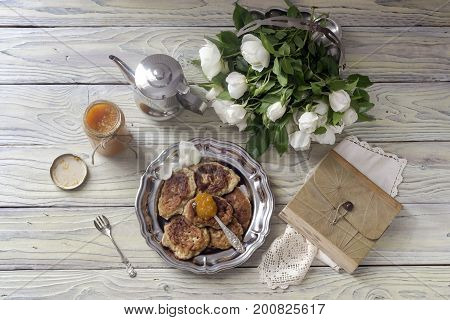 Homemade fritters, orange jam and a bouquet of white roses on a wooden table