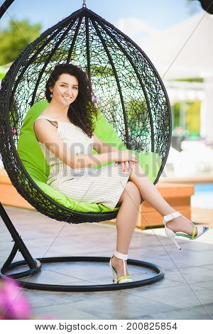 pretty brunette woman relaxing on a lounger outdoors.