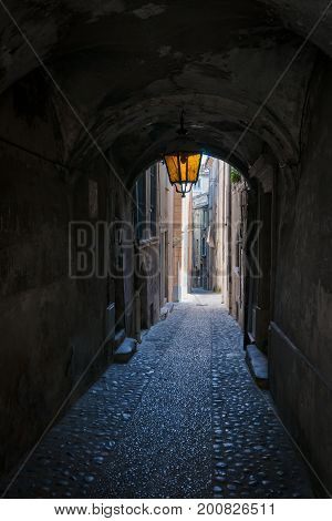 Covered arch passage in an old french medieval mountain village. An urban look with a beautiful old streetlight and arcades in a narrow alley
