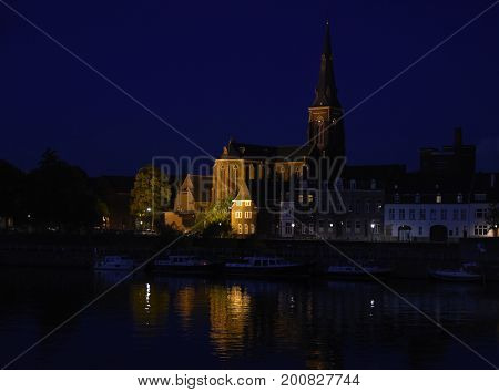 Maastricht at night the Dutch city on the river Maas with boats in the harbor and the Sint Martinuskerk church in the old town Netherlands Europe