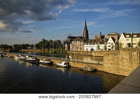 Maastricht the Dutch city on the river Maas with boats in the harbor and the Sint Martinuskerk church in the old town Netherlands Europe