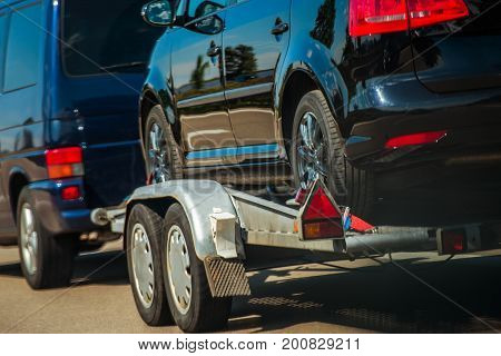 Used Cars Importing in European Union. Van Pulling Trailer with Damaged Pre Owned Vehicle For Sale in Other Country.