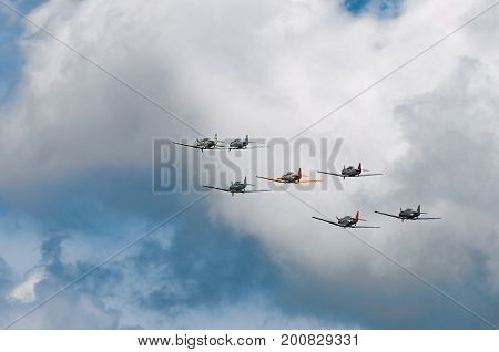 EDEN PRAIRIE MN - JULY 16 2016: Seven AT6 Texan airplanes fly away in cloudy sky at air show. The AT6 Texan was primarily used as trainer aircraft during and after World War II.