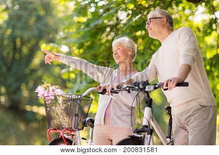 old age, people and lifestyle concept - happy senior couple walking with fixie bicycles at summer city park