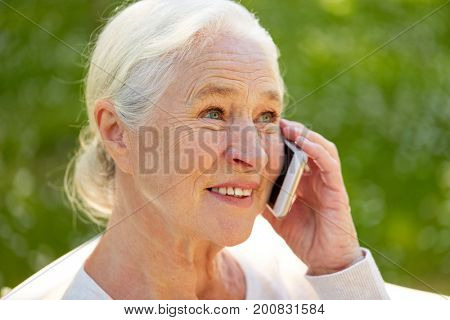 old age, retirement and people concept - close up of happy senior woman calling on smartphone in summer