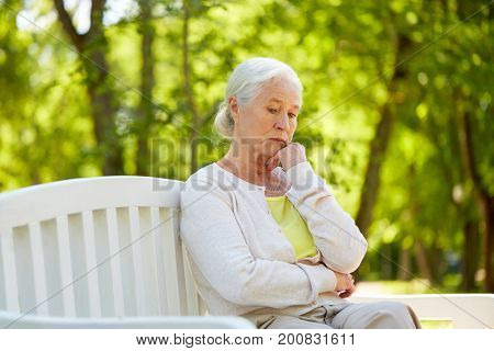 old age, retirement and people concept - sad senior woman in glasses sitting on bench at summer park