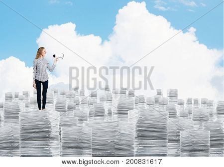 Woman in casual clothing standing on pile of documents with speaker in hand with cloudly skyscape on background. Mixed media.