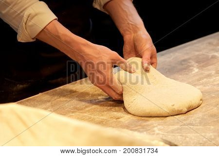 food cooking, baking and people concept - chef or baker making dough at bakery