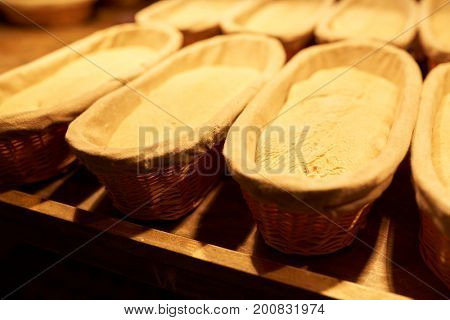 food, cooking and baking concept - yeast bread dough rising in baskets at bakery kitchen