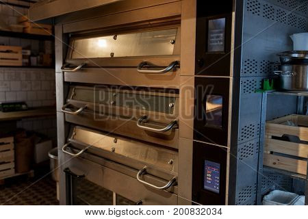 food cooking equipment and baking concept - bread oven at bakery kitchen