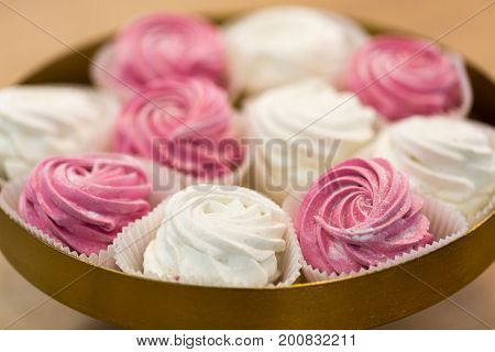 food, confection and sweets concept - close up of zephyr, marshmallow or whipped cream on cake stand