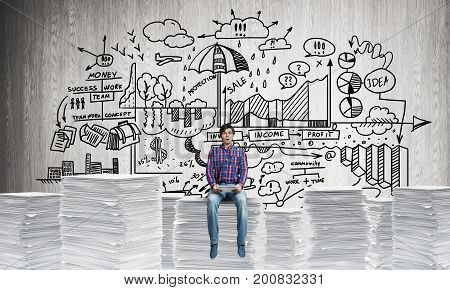 Young man in casual wear sitting on pile of documents with business-analytical information on background. Mixed media.