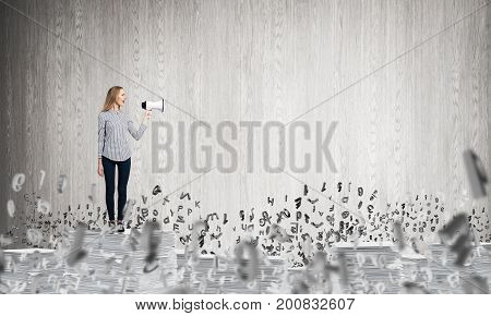 Woman in casual clothing standing among flying letters with speaker in hand and with grey wall on background. Mixed media.
