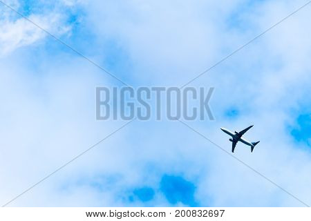Big airplane in air on blue sky. View of flying aeroplane from bottom from ground.