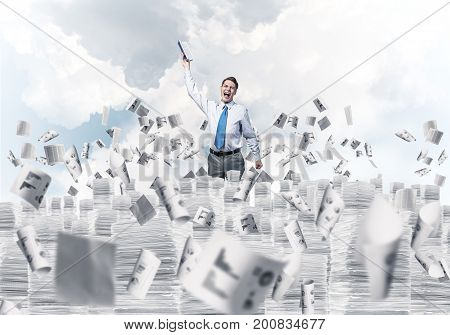 Businessman keeping hand with book up while standing among flying papers with cloudly skyscape on background. Mixed media.