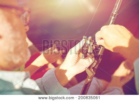 family, generation, summer holidays and people concept - senior man and child with fishing rod or spinning on river or lake berth