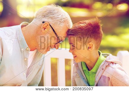 family, generation, communication and people concept - happy grandfather and grandson at summer park
