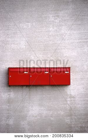 Three red stacked letterboxes on the rough concrete facade of a building.