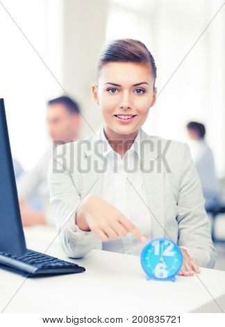 attractive businesswoman pointing at clock in office