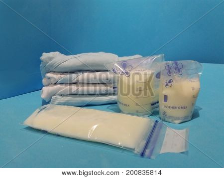 breast milk in storage bags with breast pump blue background