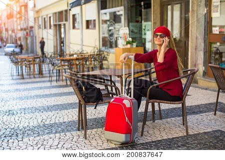 Woman with a red suitcase sitting in the street cafes.