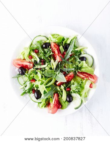 Tomato and cucumber salad with olives and pomegranate seeds