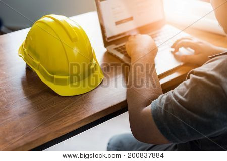 architect man working with laptop and blueprints engineer inspection in workplace for architectural plan sketching a construction project Business concept vintage color