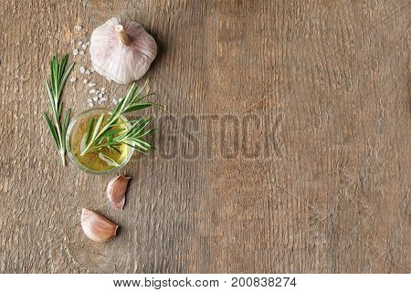 Composition with fresh rosemary, oil and garlic on wooden background