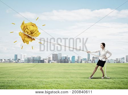 Young woman outdoors and growing paper ball presenting creativity progress