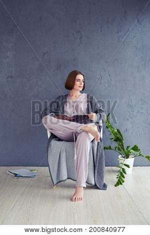 Vertical of gorgeous female reading magazine on armchair with copy space