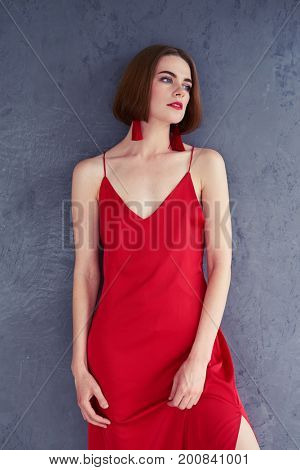Vertical of beautiful lady posing in red dress while leaning on wall