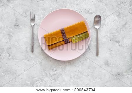 Meal is over. Pay bills. Bank card and wallet on empty plate on grey stone table top view.