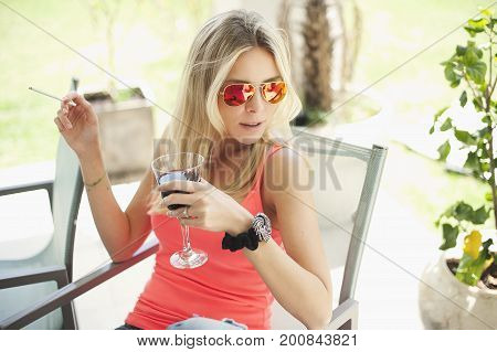 Young blond woman sitting, smoking and holding a glass of red wine