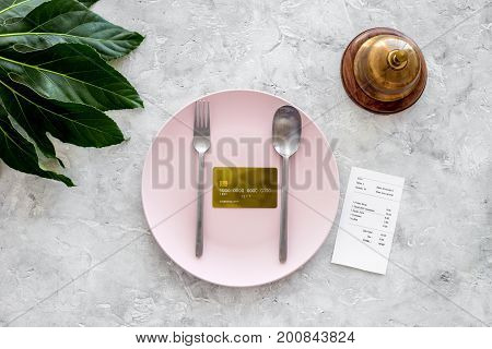 Ask for the bill at cafe. Service bell near bank card on empty plate on grey stone table top view.