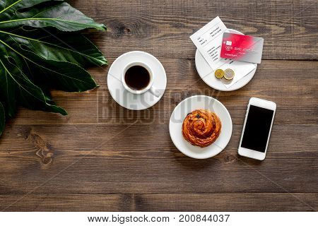 Restaurant bill and bank card near cup of coffee on dark wooden table top view.