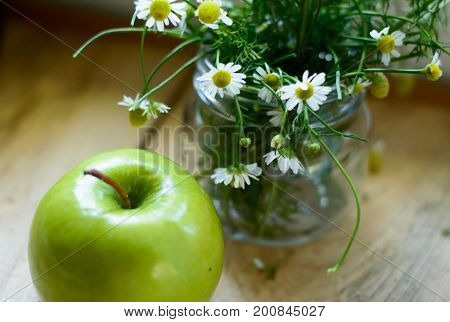 Green apple on rustic wood with jar of chamomile flowers fresh cut healthy lifestyle background, apple harvest and fall harvest fruit with organic green apple background photography poster, card or apple healthy fruit image