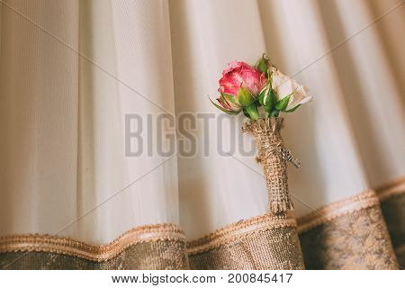 Boutonniere on a lace background. Close-up. Horizontal
